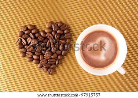 Photo of cup of coffee with shape of heart made up of beans near by