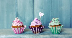 Photo of 3 cupcakes on wooden background