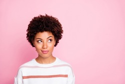 Photo of curious sly black skinned girl glancing at empty space wearing striped white sweater planning her life isolated over pink pastel color background