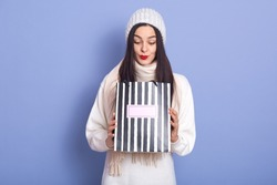 Photo of curious surprised young female holding paperbag in both hands, looking inside, standing isolated over lilac background in studio, having black hair. People and New Year presents concept.