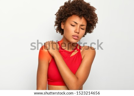 Photo of curly haired woman suffers from shoulder injury, keeps eyes closed, tilts head, touches blades, wears casual top, indicates location of pain with red spot on skin. Health problems problems