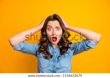 Photo of curly wavy brunette horrified feared girl in jeans denim holding her head after seeing her exams failed with face expressing disappointment isolated over yellow vibrant color background Stock foto ©
