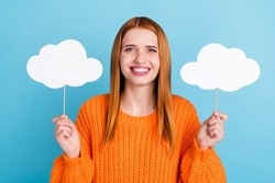 Photo of cute adorable young woman wear orange sweater holding two paper clouds smiling isolated blue color background
