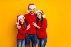 Photo of cute affectionate adorable family smiling toothily hugging each other wearing jeans denim santa cap headwear smiling toothily isolated over vivid color yellow background