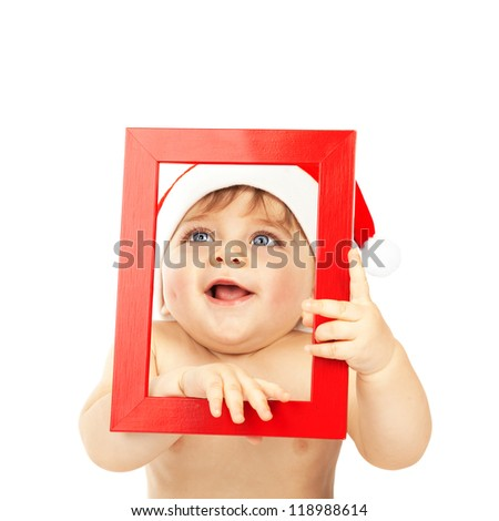 Photo of cute baby boy wearing Santa Claus hat, adorable child holding red frame in hands looking through it, pretty small kid isolated on white background, Christmas eve, New Year celebration