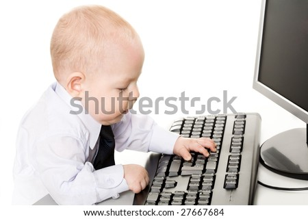 Photo of cute baby typing on keyboard with monitor in front of him