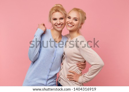 Photo of cute blonde twin sisters in identical cardigans of different colors, hugging each other, happy and funny, smiles broadly stads over pink background.