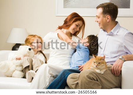 Photo of cute boy embracing his pretty mother surrounded by playful daughter and their father