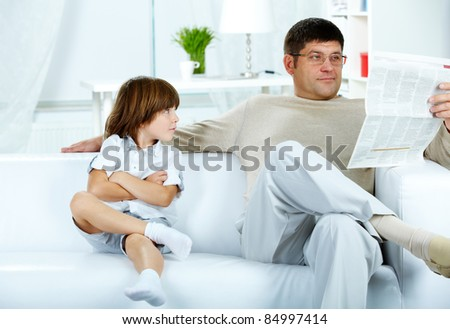 Photo of cute boy looking at his father reading paper at home