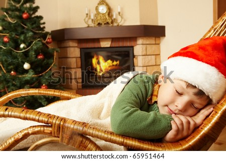 Photo of cute infant wearing santa cap sleeping in rocking chair under blanket