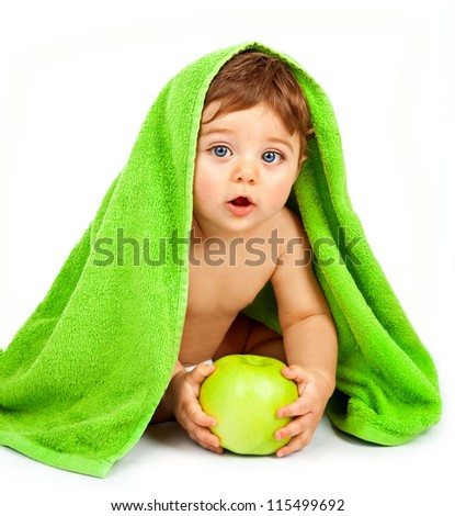 Photo of cute little boy eating big fresh apple, adorable child covered green towel isolated on white background, closeup portrait of cheerful kid enjoying healthy nutrition, health care concept