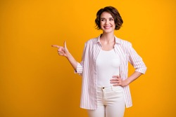 Photo of cute lovely student girl hand hip point finger look empty space, certain sure advising perfect promotion smiling wear white striped shirt isolated yellow vivid color background