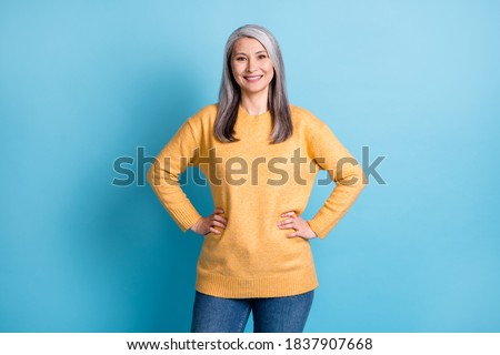 Photo of cute pretty aged lady white grey hairdo hands hips genuine gentle smile babysitting grandchildren reliable helpful wear yellow sweater isolated blue pastel color background