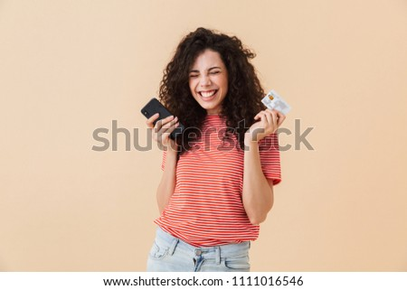 Photo of cute pretty young curly woman isolated over beige background using mobile phone holding credit card.