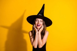 Photo of cute pretty young lady eyes closed open mouth hands face hear flattery complimented fall theme event wear black witch costume cone headwear isolated yellow color background