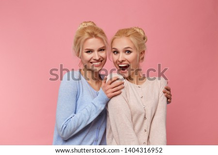 Photo of cute twins blondes, posing for a family album and photos to send them to grandma. Having fun and smiling widely into the camera, stands over pink background.