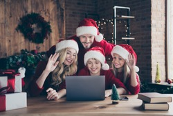Photo of dad mom and two children making x-mas eve skype video meeting conference waving arms congratulating relatives sitting table indoors wear red jumpers santa claus caps