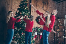 Photo of dad mom and two children spending x-mas morning together pretending air flight hanging garland baubles on newyear tree indoors wear red sweaters