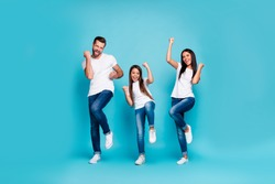 Photo of daddy mommy and small lady raising fists air rejoicing wear casual outfit isolated blue background