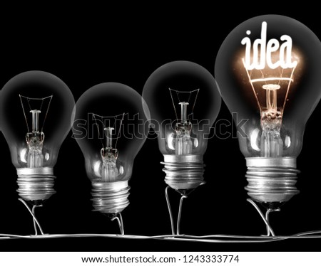 Photo of dark and shining light bulbs with fibe in IDEA shape; concept of idea, innovation, uniqueness and standing out; isolated on black background #1243333774