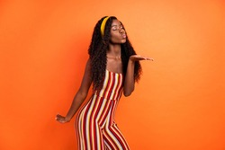 Photo of dark skin stunning charming woman send air kiss empty space hand isolated on orange color background
