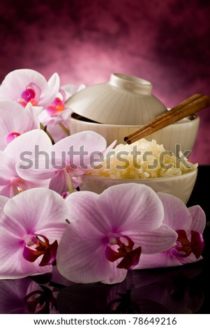 photo of delicious asian rice dish with orchid flowers around