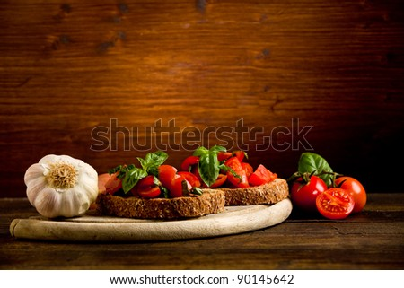 photo of delicious bruschetta appetizer with fresh cutted tomatoes and basil