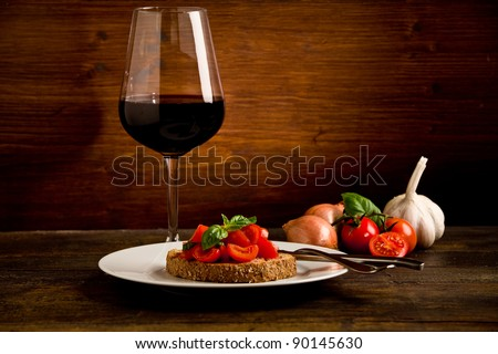 photo of delicious bruschetta appetizer with red wine glass on wooden table - stock photo