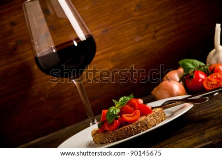 photo of delicious bruschetta appetizer with red wine glass on wooden table