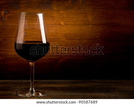 photo of delicious dark red wine goblet on wooden table illuminated by spot