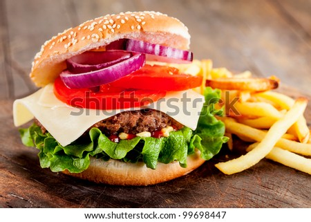 photo of delicious hamburger with fries on wooden table