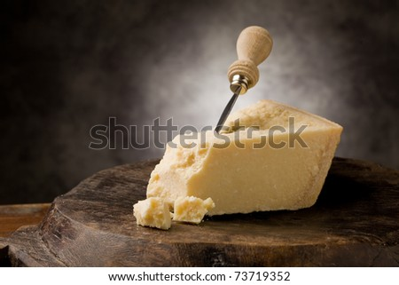 photo of delicious italian parmesan cheese with knife on wooden table - stock photo