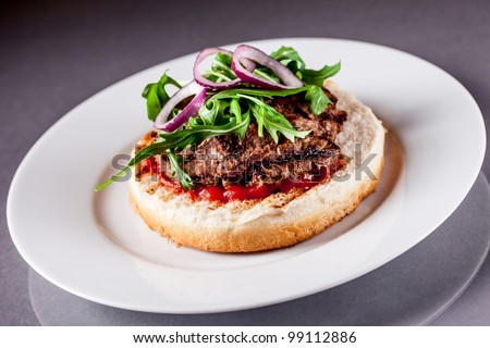 Photo of delicious light burgher with meat and arugula salad