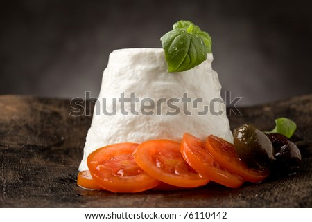 photo of delicious ricotta cheese with tomatoes on wooden table with basil