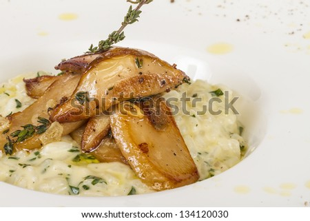 photo of delicious risotto dish with herbs and mushrooms on white background