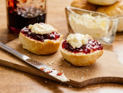 Photo of delicious scones on a plate with clotted cream and jam.