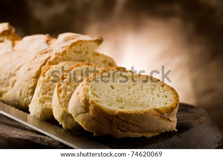 photo of delicious sliced bread on wooden table with knife