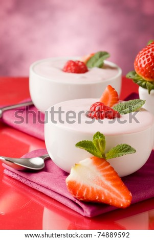 photo of delicious strawberry yogurt on red glass table