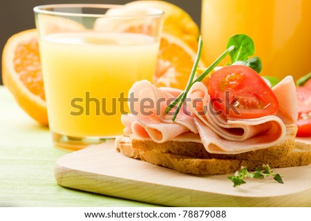 photo of delicious toast with ham on wooden table with orange juice