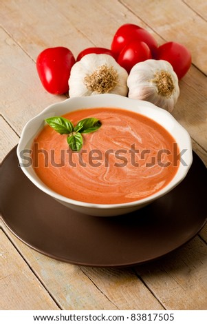 photo of delicious tomato cream soup on wooden table with garlic and basil - stock photo