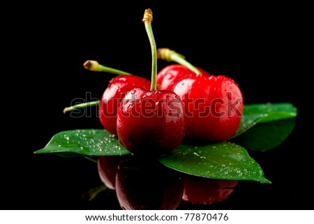 photo of delicious wet cherries on green leaves over black reflecting background