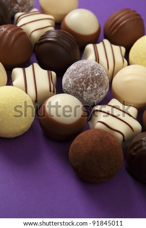 Photo of delicious white chocolates and truffles on purple table.