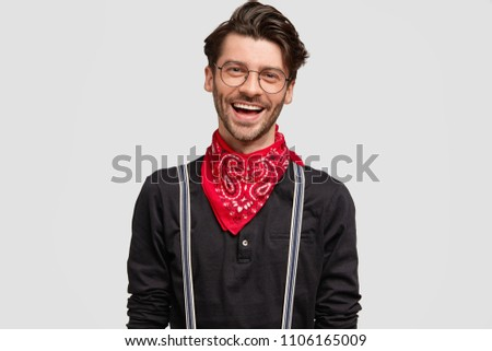 Photo of delighted handsome bearded guy with positive expression, being in good mood, rejoices success, dressed in black shirt and red bandana, isolated over white background. People and style