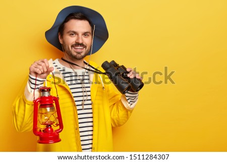 Photo of delighted man with stubble, wears headgear and yellow raincoat, carries kerosene lamp and binoculars, looks gladfully at camera, stands indoor. People, expedition, traveling, pastime concept