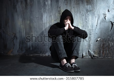 Photo of desperate young drug addict wearing hood and sitting alone in dark