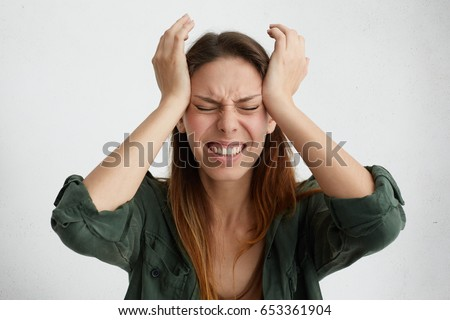 Photo of disappointed woman holding her hands on temples frowning face having wide opened mouth and closed eyes screaming in despair and terror. Woman regreting her act. Female in despair and shock Foto stock ©