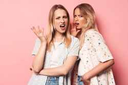 Photo of displeased confused pretty blondes women friends posing isolated over pink wall background talking with each other.
