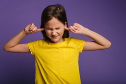 Photo of displeased pretty girl posing and plugging her ears isolated over purple background