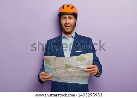 Photo of dissatisfied man builder director holds map, studies location for new construction, unhappy to choose not appropriate place, wears headgear and formal suit, poses over purple studio wall