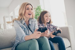 Photo of domestic funny blond lady mom daughter sitting comfy couch hold joystick playing video games stay home safety quarantine spend weekend together best friends living room indoors
